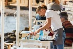 Een mannelijke kelner die een lijst ontruimen in openlucht bij een Griekse herberg in de waterkant van Mykonos, Griekenland stock afbeelding