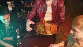 Een mannelijke kelnersbarman brengt een alcoholcocktail aan een bedrijf van jonge vrienden stock footage