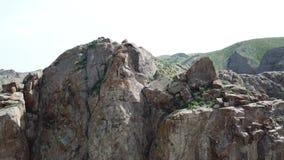 Een mannelijke klimmer beklimt op de klip Het schieten vindt aan de kant van de lucht plaats Opent een mooie mening van de rots,  stock videobeelden