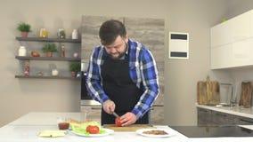 Een mannelijke kok in een schort snijdt een tomaat in de keuken, op de lijst zijn de ingrediënten voor een hamburger, langzame mo stock footage