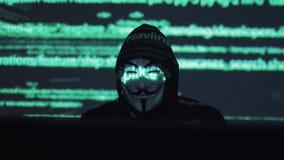 Een mannelijke rover in het maskerwerk aangaande een computer in een donkere ruimte de computercode wordt overdacht zijn gezicht  stock videobeelden