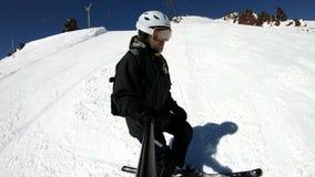 Een mannelijke skiër van de selfie brede hoek verouderde in zwart materiaal en witte helmritten op een sneeuwhelling op een zonni stock videobeelden