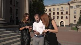 Een mannelijke student en twee vrouwelijke studenten lopen langs de straat en spreken aan elkaar stock videobeelden