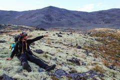 Een mannelijke toerist is vermoeid en zit op een mos in de bergen in een stijging met een vinger toont de richting royalty-vrije stock afbeelding