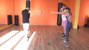 Een mannelijke vechtsportentrainer onderwijst een mens en een meisje om directe domooroefeningen, langzame mo, schaduw-in dozen d stock videobeelden
