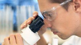 Een mannelijke wetenschapper die in een laboratorium met microscoop werken stock video