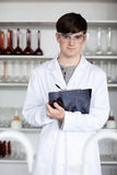 Een mannelijke wetenschapsstudent die op een klembord schrijft Royalty-vrije Stock Foto