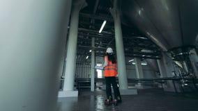 Een mannetje en vrouwelijke ingenieurs heeft een gesprek in brouwerijeenheid stock videobeelden