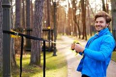 Een mant die in een park met de stroken van de trxgeschiktheid uitoefenen Royalty-vrije Stock Afbeeldingen