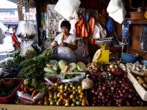 Een marktverkoper binnen een fruit en plantaardige box in een openbare markt royalty-vrije stock afbeelding