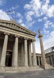 Een marmeren kolom met beeldhouwwerken van Apollo tegen een blauwe hemel met wolken in de Atheense Academie royalty-vrije stock fotografie