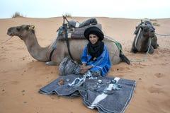 Een Marokkaanse jongens verkopende herinneringen in Merzouga, die op de rand van Erg Chebbi in Marokko ligt Stock Foto's