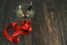 Een martini-glas met een olijf en scharlaken lint op een houten lijst royalty-vrije stock afbeelding
