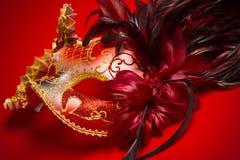 Een maskeren rode, gouden en zwarte mardigras op een rode achtergrond stock afbeeldingen