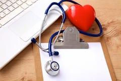 Een medische stethoscoop dichtbij laptop op houten Stock Foto's