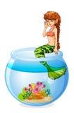 Een meerminzitting boven het aquarium stock illustratie