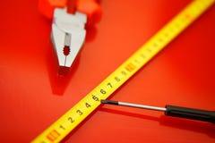 Een meetlint, een schroevedraaier-kraan en de buigtang liggen op een rode opgepoetste oppervlakte in een autoreparatiewerkplaats  stock fotografie