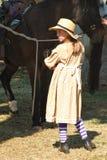 Een meisje in 1860's periodekostuum neigt aan paarden Stock Fotografie