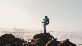 Een meisje, een alpinist, die zich op een klip met Wandeling bevinden plakt, leunt tegen hen van moeheid en vindt binnen plaats stock videobeelden