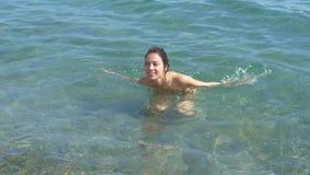 Een meisje baadt in het overzees, plonsen van water, het slow-motion schieten Meisje in een zwempak stock footage