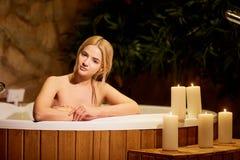 Een meisje in een badpak in een Jacuzzi met kaarsen stock foto