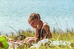 Een meisje in een badpak zit eenzaam op het strand op het gras dichtbij de rivier op een zonnige dag Het meisje is droevig op het stock foto's