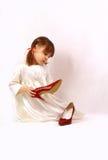 Een meisje bekijkt de grote schoenen Royalty-vrije Stock Foto