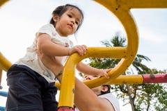 Een meisje beklimt de hoge gele ladder bij speelplaats op een zon Stock Foto's