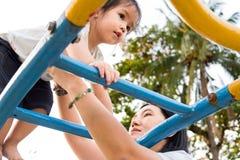 Een meisje beklimt de hoge gele ladder bij speelplaats op een zon Royalty-vrije Stock Foto