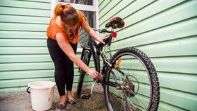 Een meisje bereidt een fiets op het seizoen voor stock footage