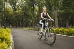 Een meisje berijdt een Fiets op de fietsweg Stock Foto
