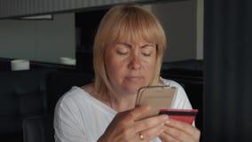 Een meisje betaalt voor een online aankoop Betaling voor online aankopen op Internet die een smartphone gebruiken stock footage