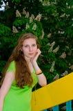 Een meisje bevindt zich bij de bloeiende kastanje Stock Fotografie