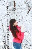 Een meisje bevindt zich dichtbij de snow-covered bomen kijkt upwards Royalty-vrije Stock Foto