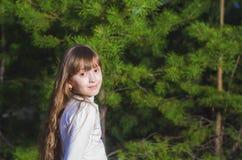 Een meisje bevindt zich op de achtergrond van spar Royalty-vrije Stock Afbeelding