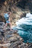 Een meisje bevindt zich op de rand van een klip dichtbij de oceaan in een sterke wind royalty-vrije stock afbeelding