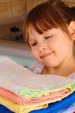 Een meisje bewondert de handdoeken na was Royalty-vrije Stock Foto's