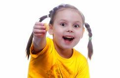 Een meisje biedt een stuk van koekje aan Stock Foto's