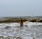 Een meisje in een blauw zwempak op het gele overzees stock foto's