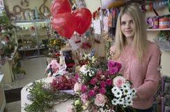 Een meisje, een bloemist-ontwerper houdt een mooi, feestelijk boeket van rode bloemen en een hart met de inschrijvingsliefde stan royalty-vrije stock afbeeldingen