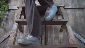 Een meisje in broeken en tennisschoenen daalt van een houten ladder: benenclose-up stock afbeelding
