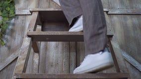 Een meisje in broeken en tennisschoenen neemt tot een houten trapladder toe: benenclose-up stock afbeelding