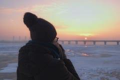 Een meisje in een bruin jasje en een bruine wollen hoed met grote pompon drinkt meeneemkoffie en horloges de zonsopgang in Kyiv,  Royalty-vrije Stock Afbeeldingen
