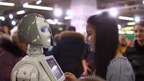 Een meisje communiceert met een vrouwelijke robot en glimlacht Moderne robotachtige technologieën Kunstmatige intelligentie cyber stock footage