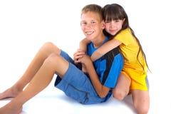 Een meisje dat een jongen een grote omhelzing geeft Stock Afbeelding