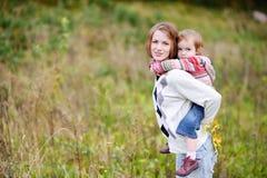 Een meisje dat een vervoer per kangoeroewagenrit op haar mamma heeft Stock Foto's