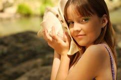 Een meisje dat een zeeschelp luistert Royalty-vrije Stock Foto's