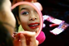 Een meisje dat met make-up speelt stock foto's