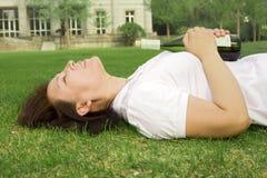 Een meisje dat op gras legt Stock Foto's