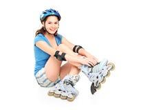 Een meisje dat op rolschaatsen zet royalty-vrije stock afbeeldingen